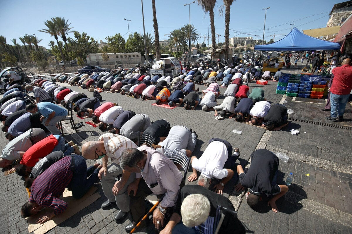 JERUSALEM - OCTOBER 16: Palestinians, who weren't allowed to enter Al-Aqsa Mosque by Israeli forces as people outside of Old City were not let through as part of the three-week lockdown measures against coronavirus (COVID-19) pandemic, perform Friday prayer outside the Damascus Gate in Jerusalem on October 16, 2020. ( Mostafa Alkharouf - Anadolu Agency )