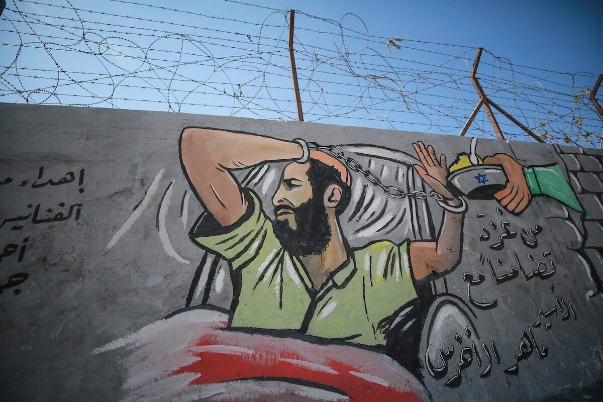 A painting wall shows Palestinian prisoner in Israeli jail Maher Al-Akhras, who has been on a hunger strike for 84 days, rejecting the food, at Nuseirat Refugee Camp in Gaza City, Gaza on 18 October 2020. [Mustafa Hassona - Anadolu Agency]