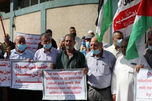 Palestinians hold banners during a demonstration demanding United Nations Relief and Works Agency for Palestine Refugees in the Near East (UNRWA) to continue its operations in Gaza City, Gaza on 20 October 2020. [Mustafa Hassona - Anadolu Agency]