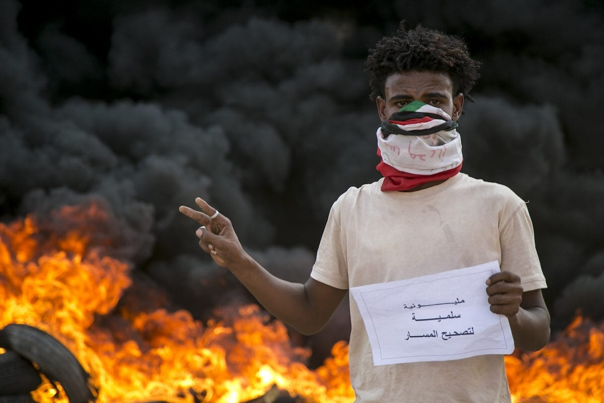 A protester poses in front of burning tyres during a protest against economic crisis and high cost of living in Khartoum, Sudan on 21 October 2020. [Mahmoud Hjaj - Anadolu Agency]