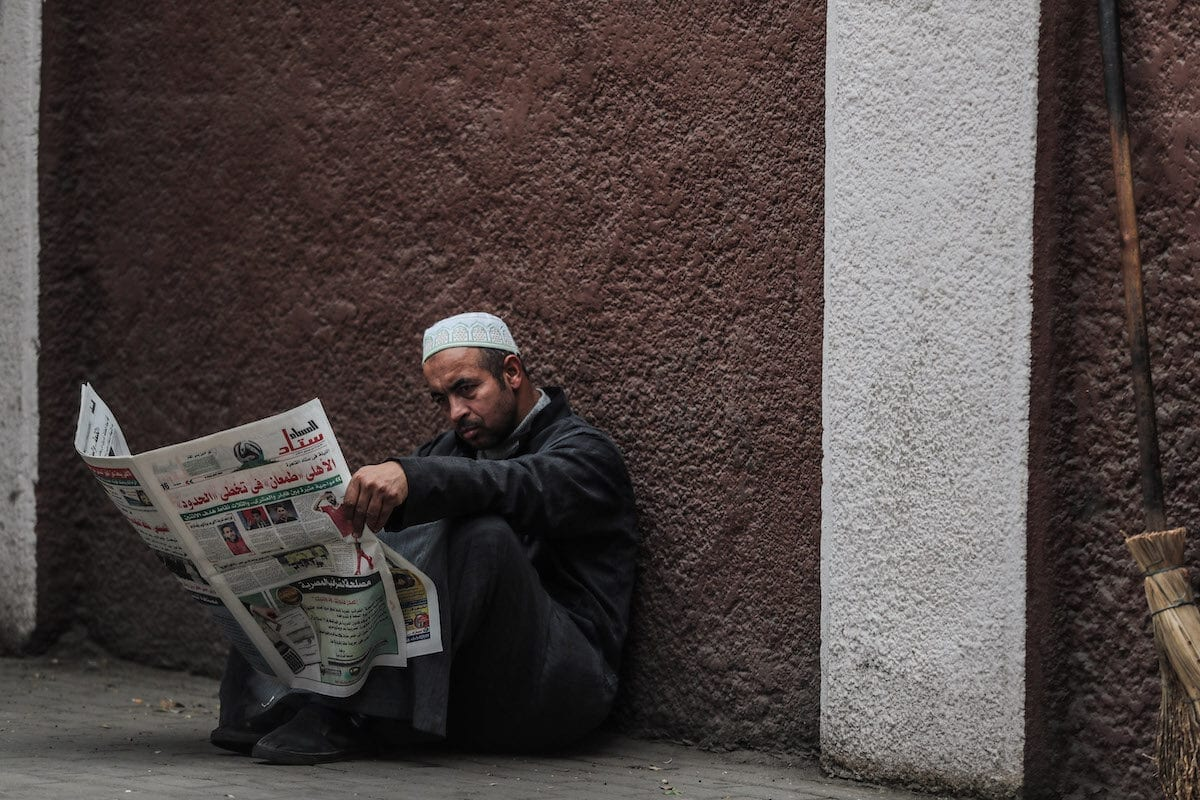 A man reads a newspaper on a sidewalk in the Zamalek district of western Cairo on 15 December 2019. [MOHAMED EL-SHAHED/AFP via Getty Images]