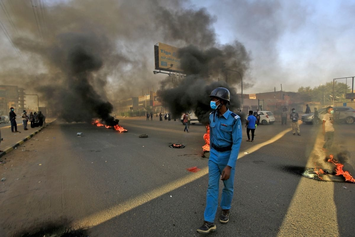 A mask-clad policeman walks near tires set aflame by Sudanese protesters marking the first anniversary of a raid on an anti-government sit-in, in the Riyadh district in the east of the capital Khartoum on 3 June 2020. [ASHRAF SHAZLY/AFP via Getty Images]