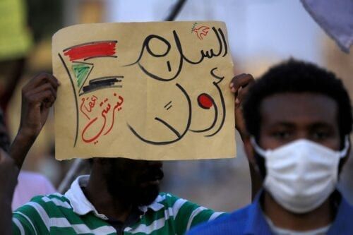 "A demonstrator holds up a sign reading in Arabic ""peace first, Nertiti sit-in"" along with a drawn Sudanese flag, during a protest outside the Sudanese Professionals Association in the Garden City district of Sudan's capital Khartoum on 4 July 2020, in solidarity with the people of the Nertiti region of Central Darfur province in the country's southwest. [ASHRAF SHAZLY/AFP via Getty Images]"