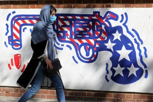A woman, wearing a protective mask amid the COVID-19 pandemic, walks past a mural painted on the outer walls of the former US embassy in the Iranian capital Tehran on 20 September 2020. [ATTA KENARE/AFP via Getty Images]