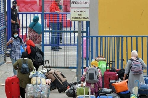 Moroccan nationals, stranded in Spain since the closure of borders in mid-March to tackle the coronavirus, go through customs prior to crossing the Spanish-Moroccan border in the Spanish enclave of Ceuta on 30 September 2020. [ANTONIO SEMPERE/AFP via Getty Images]