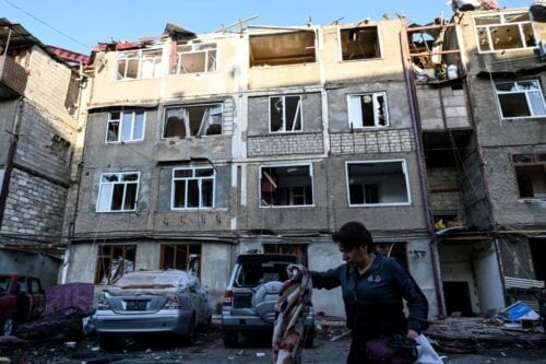 A woman carrying her belongings walks away from an apartment building that was supposedly damaged by recent shelling in the breakaway Nagorno-Karabakh region's main city of Stepanakert on October 3, 2020, during the ongoing fighting between Armenia and Azerbaijan over the disputed region [ -/AFP via Getty Images]