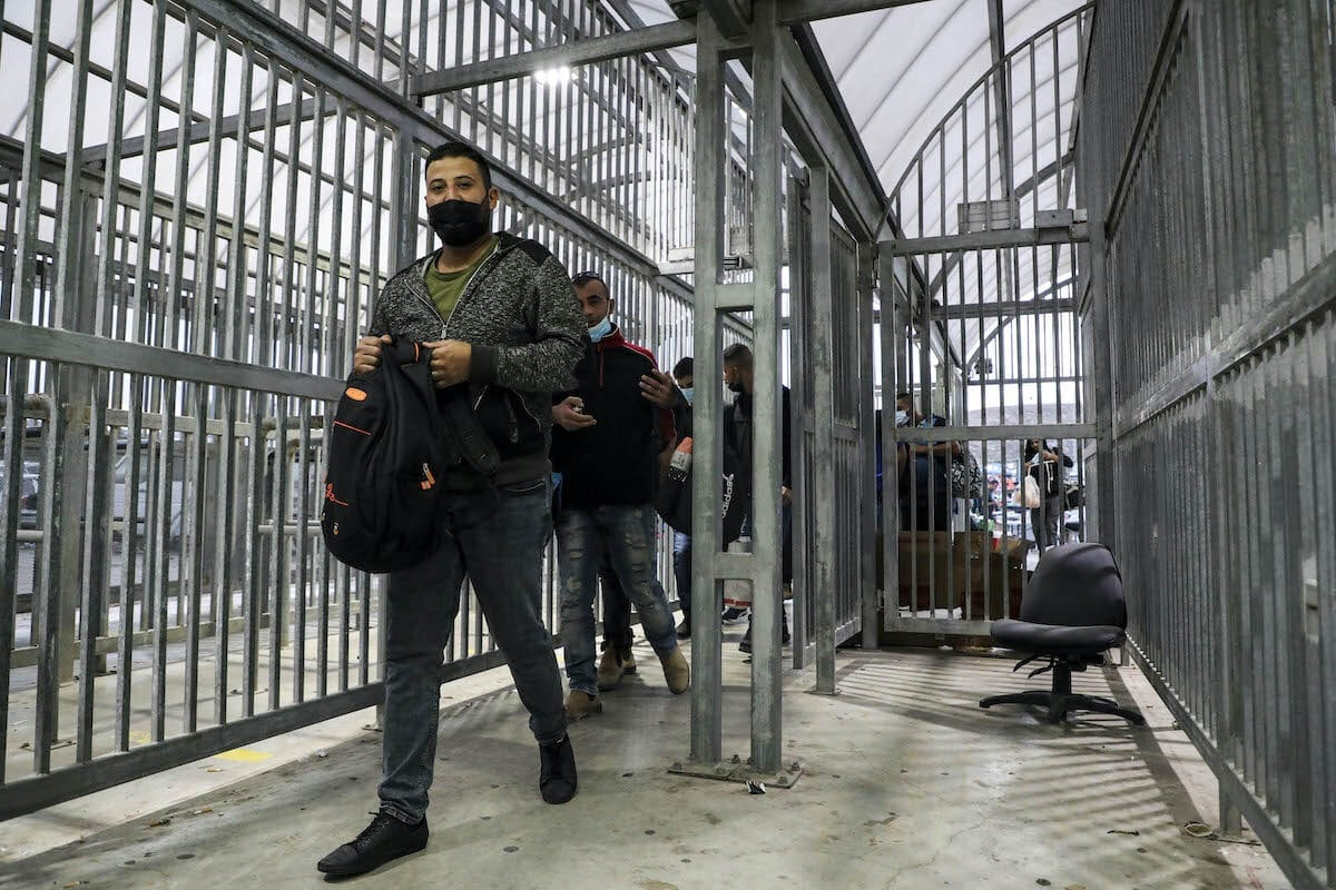 Palestinians workers at a checkpoint in the West Bank on 4 October 2020 [HAZEM BADER/AFP/Getty Images]