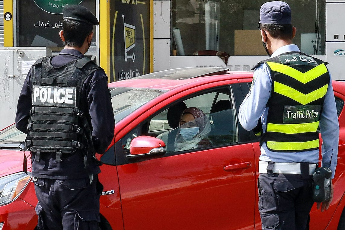 Jordanian policemen stop a vehicle and check the identification documents of its driver at a checkpoint during a COVID-19 coronavirus lockdown in the capital Amman on 9 October 2020. [KHALIL MAZRAAWI/afp/AFP via Getty Images]