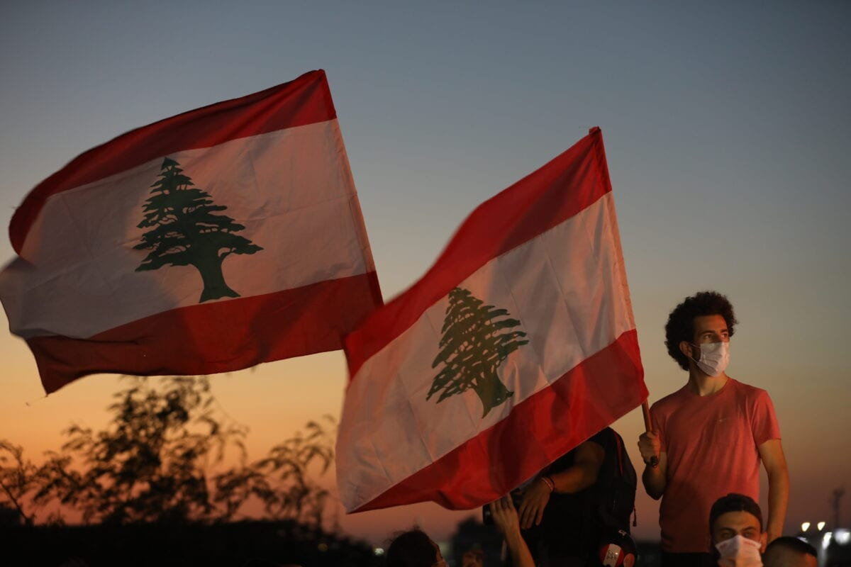 People wave Lebanese flags to mark the one-year anniversary of anti-government protests in Beirut, Lebanon on 17 October 2020 [Marwan Tahtah/Getty Images]