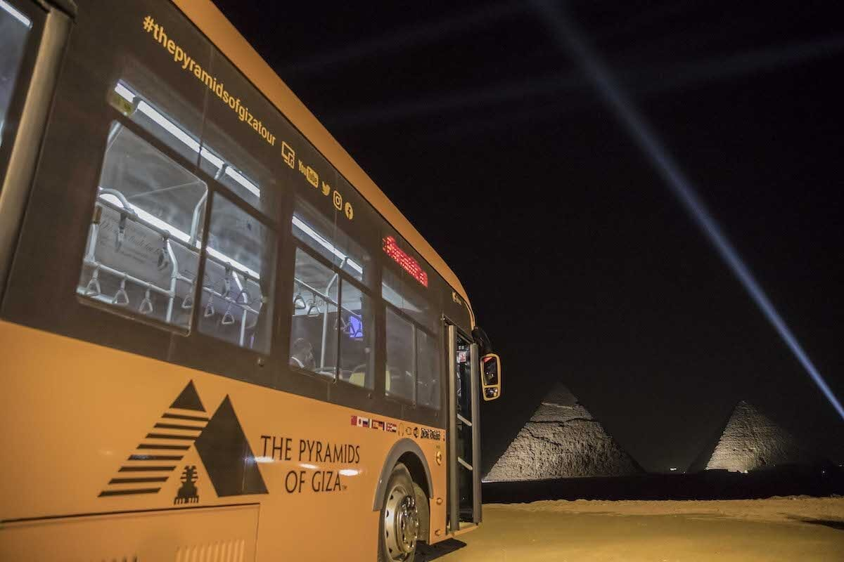 A general view of (background R to L) the Great Pyramid of Khufu (Cheops) and the Pyramid of Khafre (Chephren) at the Giza Pyramids necropolis on the southwestern outskirts of the Egyptian capital Cairo during an official ceremony launching the trial operations of the site's first environmentally-friendly electric bus (foreground) and restaurant as part of a wider development plan at the necropolis on 20 October 2020 [KHALED DESOUKI/AFP via Getty Images]