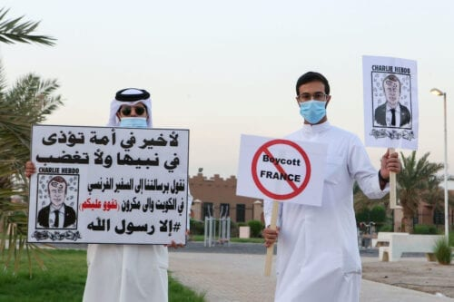 Kuwaitis lift placards expressing anger at French President Emmanuel Macron in Kuwait City, on 24 October 2020 [AFP/Getty Images]