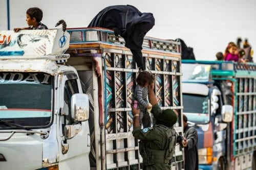 A Kurdish fighter helps a Syrian child to board a truck at the Kurdish-run al-Hol camp, transporting Syrian women and children suspected of being related to Daesh (ISIS) terrorist group, after being released from the camp to return to their homes, in the al-Hasakeh governorate in northeastern Syria, on 28 October 2020. [DELIL SOULEIMAN/AFP via Getty Images]