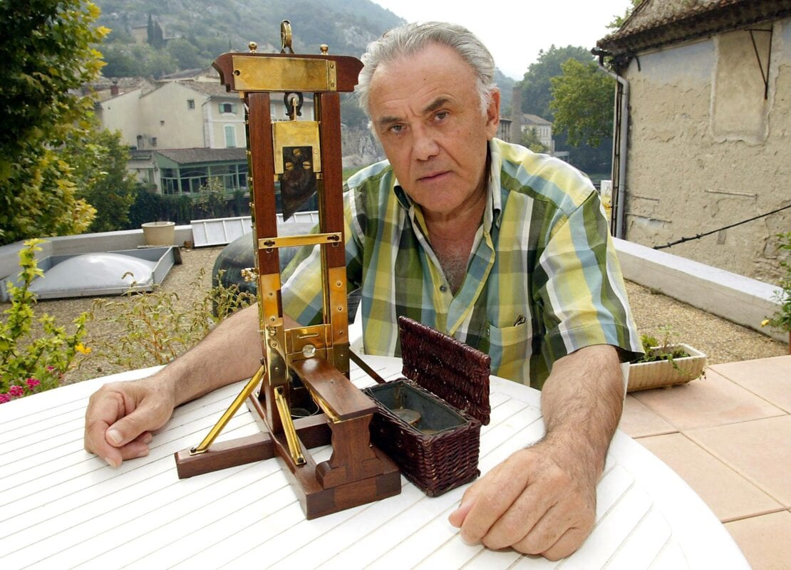 """TO GO WITH FRENCH AFP STORY : """"PEINES ET CHATIMENTS : LA COLLECTION D'UN BOURREAU AUX ENCHERES A PARIS """" A file picture taken on September 20, 2002, shows France's last surviving executioner in Algeria Fernand Meyssonnier showing the miniature replica of a guillotine in Fontaine-de-Vaucluse, southern France. He made this replica at the age of 15 as a present for his father who was chief executioner and inducted his son as an apprentice in 1947. AFP PHOTO GERARD JULIEN (Photo credit should read GERARD JULIEN/AFP via Getty Images)"""