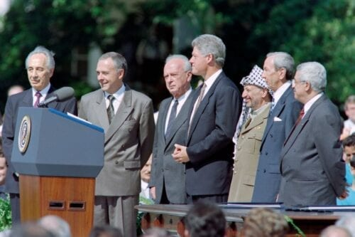 US President Bill Clinton (4th R) prepares to give the opening address of the historic Israel-PLO Oslo Accords signing ceremony on September 13, 1993 at the White House in Washington, D.C. next to Israeli Foreign Minister Shimon Peres (L), Russian Foreign Minister Andrei Kozyrev (2nd L), Israeli Prime Minister Yitzhak Rabin (3rd L), PLO Chairman Yasser Arafat (3rd R), US Secretary of State Warren Christopher (2nd R) and PLO political director Mahmoud Abbas (R). [LUKE FRAZZA/AFP via Getty Images]