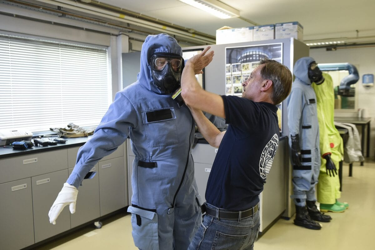A man tries on safety equipment during a simulation at the OPCW (The Organisation for the Prohibition of Chemical Weapons) headquarters in The Hague, The Netherlands, on April 20, 2017 [JOHN THYS/AFP via Getty Images]