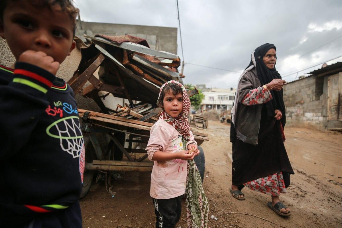 Children are seen at muddy road after rainfall in Gaza City, Gaza on 5 November 2020 [Mustafa Hassona/Anadolu Agency]