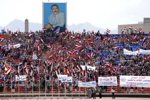 Thousands of Yemenis wave their national flag as they sit under a huge portrait of President Ali Abdullah Saleh during National Day celebrations at Sanaa's main stadium on April 24, 2010 [MOHAMED HUWAIS/AFP via Getty Images]