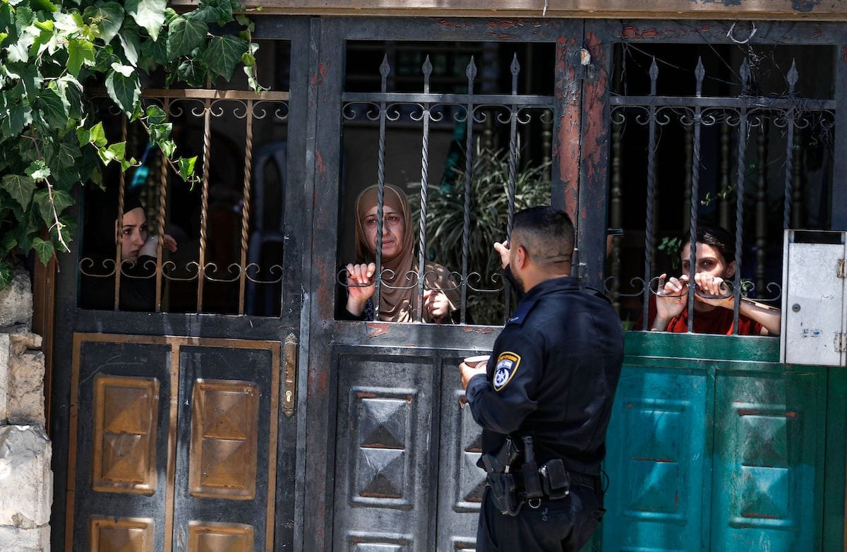 An Israeli policeman stands outside the former house of a Palestinian family as some of their members look from a gate, during their eviction in the Palestinian neighbourhood of Silwan in east Jerusalem near the Old City on 10 July 2019. [AHMAD GHARABLI/AFP via Getty Images]