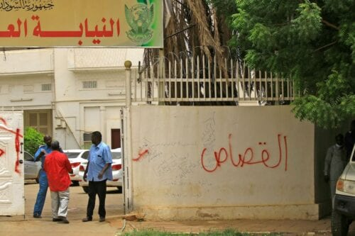 "A security man stands guard outside Sudan's Attorney General headquarters, which is sprayed with a graffiti that reads in Arabic ""retribution"", in the capital Khartoum on 15 June 2020. [ASHRAF SHAZLY/AFP via Getty Images]"