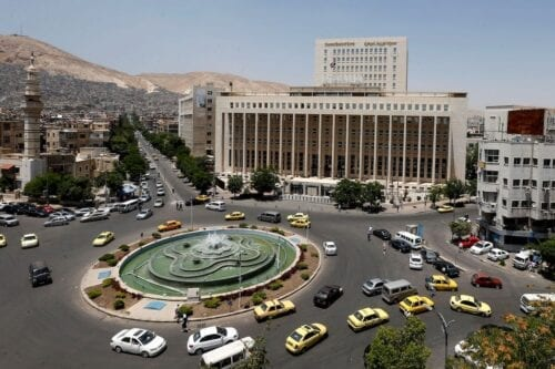 Vehicles drive along the roundabout past the Central bank of Syria in the capital Damascus' Sabaa Bahrat Square on 17 June 2020. [LOUAI BESHARA/AFP via Getty Images]