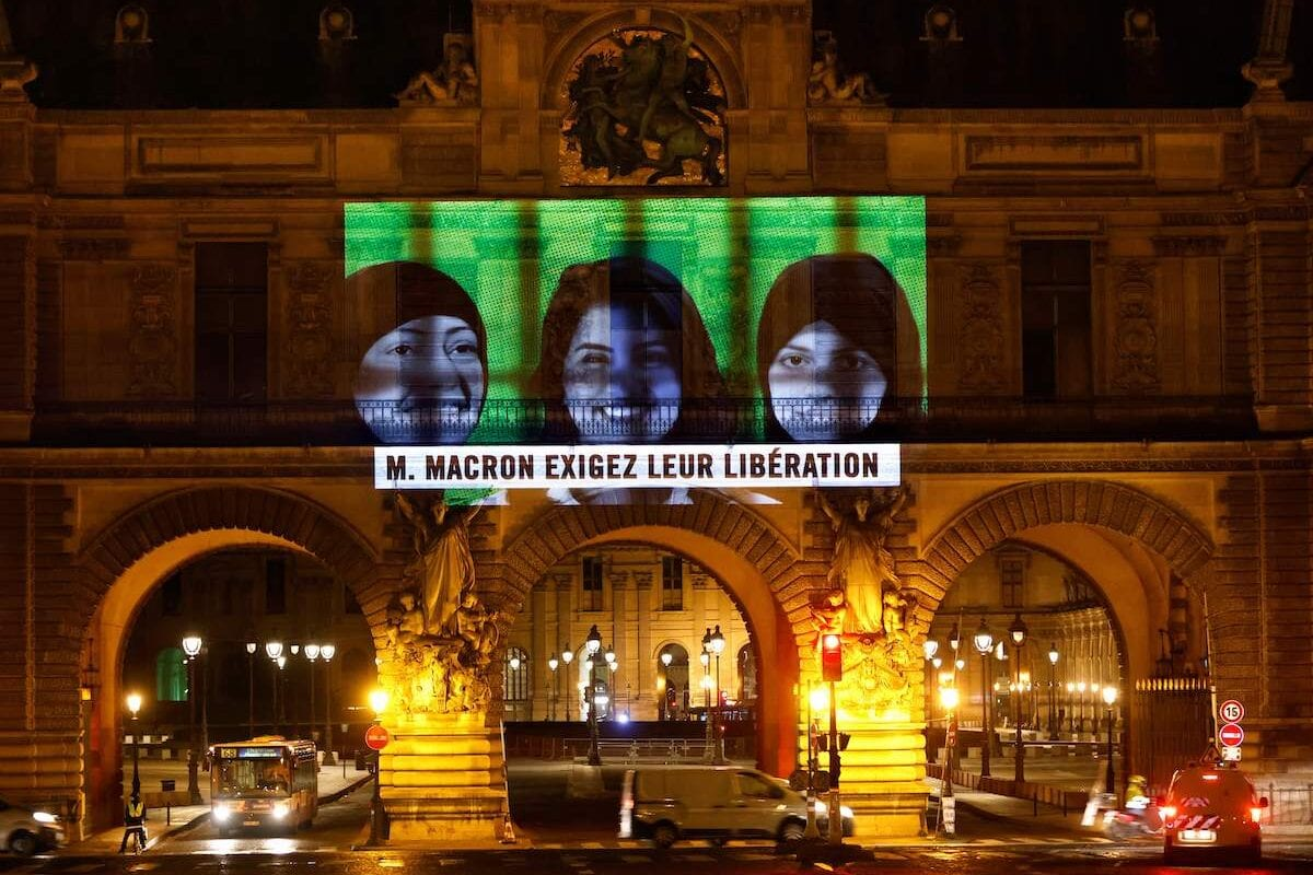"""A projection on the Louvre Museum in Paris by Amnesty International members depicting jailed Saudi human rights activists including Loujain Al-Athloul (C) and reading """"Mr Macron, demand their release"""", ahead of the upcoming virtual G20 summit, on 19 November 2020 [THOMAS COEX/AFP via Getty Images]"""