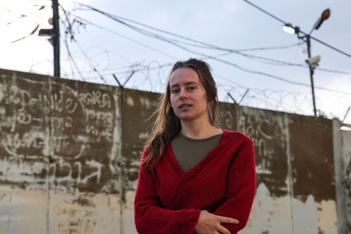 """Hallel Rabin, a 19-year-old Israeli conscientious objector, poses for a picture outside the """"number six"""" military prison near Atlit in northern Israel on November 20, 2020, upon release from jail for refusing to serve in the Israeli army. - Army service is compulsory for most Israeli citizens and while many seek exemptions on various grounds -- some arguably less than truthful -- Rabin's case is unusual in that she openly declared herself to be a pacifist and served prison time. Hallel had served a total of 56 days since August at the grim military prison """"number six"""", and was facing up to 80 more in detention. But after grilling her at four hearings, an army board finally accepted that her pacifism was sincere and not driven by """"political considerations,"""" which would have landed her more prison time. (Photo by Emmanuel DUNAND / AFP) (Photo by EMMANUEL DUNAND/AFP via Getty Images)"""