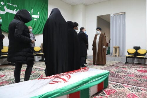 """Iran's Judiciary Chief Ayatollah Ebrahim Raisi (R) pays respects to the body of slain scientist Mohsen Fakhrizadeh among his family, in the capital Tehran on November 28, 2020. - Mohsen Fakhrizadeh, dubbed by Israel as the """"father"""" of Iran's nuclear programme, died on November 27 after being seriously wounded when assailants targeted his car and engaged in a gunfight with his bodyguards outside Tehran, according to Iran's defence ministry. The assassination comes less than two months before US President-elect Joe Biden is due to take office, after a tumultuous four years of hawkish foreign policy in the Middle East under President Donald Trump. (Photo by - / MIZAN NEWS AGENCY / AFP) (Photo by -/MIZAN NEWS AGENCY/AFP via Getty Images)"""