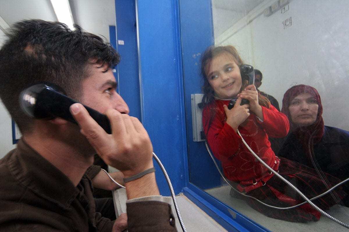 GILBOA PRISON, Israel: A Palestinian prisoner sits behind glass speaking on a telephone to a young relative 05 March 2006 at the Gilboa prison, east of the northern Israeli town of Afula. Most of the 850 adult male prisoners in this prison are serving very long jail terms and some are serving life sentences for taking part in militant acts. AFP PHOTO/Hagai AHARON-ISRAEL OUT (Photo credit should read HAGAI AHARON/AFP via Getty Images)