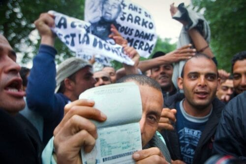A Tunisian citizen shows his passport on in Paris, during a demonstration to protest against French state's politics regarding Tunisian migrants on 28 April 2011 [JOEL SAGET/AFP /Getty Images]