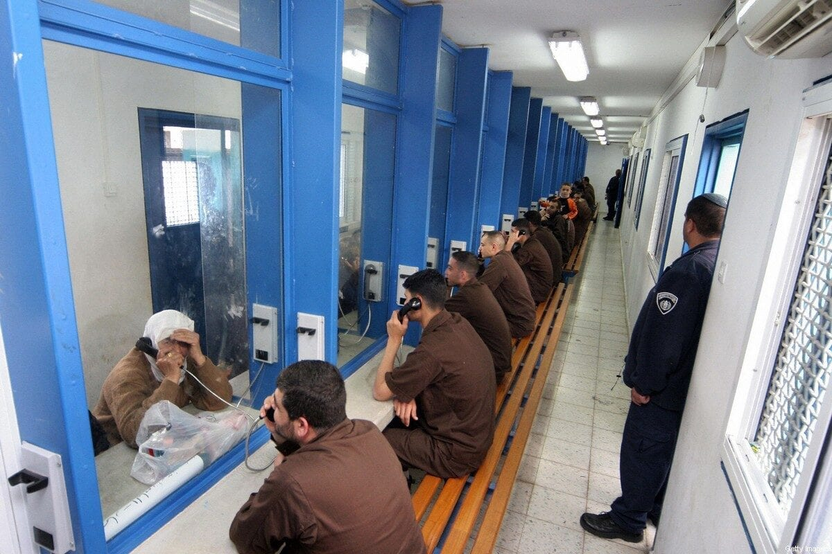Palestinian men sit in their brown prison uniforms behind glass talking on phones to relatives 05 March 2006 at the Gilboa prison, Israel [HAGAI AHARON/AFP via Getty Images]